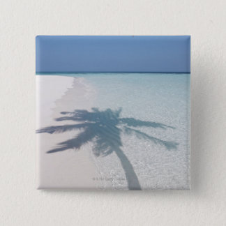 Shadow of a palm tree on a deserted island beach pinback button