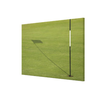 shadow of golf flag on golf course green canvas print