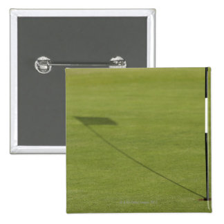 shadow of golf flag on golf course green pinback button