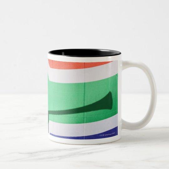 Shadow of soccer supporter blowing vuvuzela, Two-Tone coffee mug