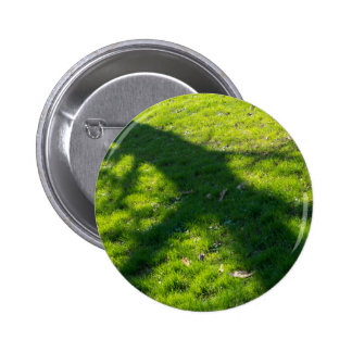 Shadow of the tree at the spring grass pinback button