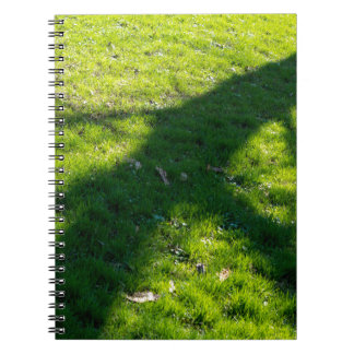 Shadow of the tree at the spring grass spiral notebook