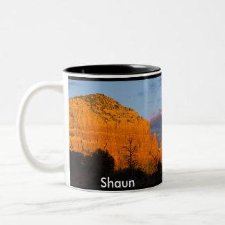 Shaun en la taza roja de la roca de la salida de l