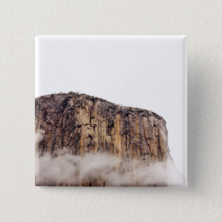 Sheer cliff rising above clouds button