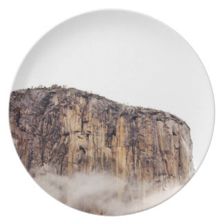 Sheer cliff rising above clouds dinner plate