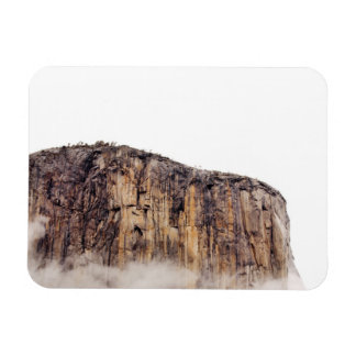 Sheer cliff rising above clouds rectangular photo magnet
