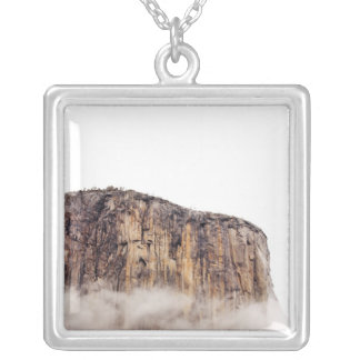 Sheer cliff rising above clouds silver plated necklace