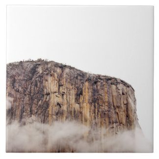 Sheer cliff rising above clouds large square tile