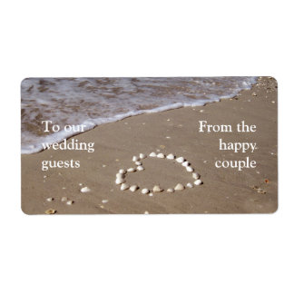 Shell heart on sandy beach label
