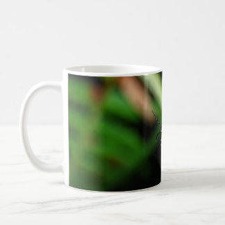 Shining red beetle in the green leaf coffee mug