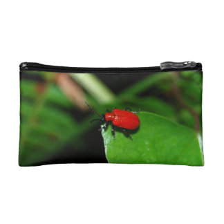 Shining red beetle in the green leaf makeup bag