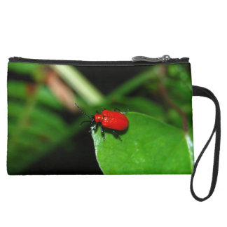 Shining red beetle in the green leaf suede wristlet