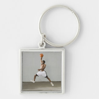 shirtless man jumping with a basketball keychain