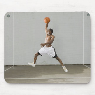 shirtless man jumping with a basketball mouse pad