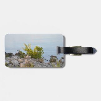 shoreline with rocks and plants of river luggage tag
