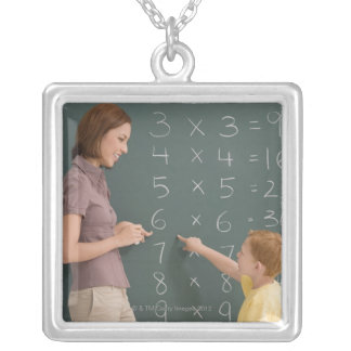 Side profile of a female teacher teaching her silver plated necklace
