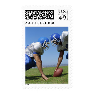 side profile of two football players playing on stamp