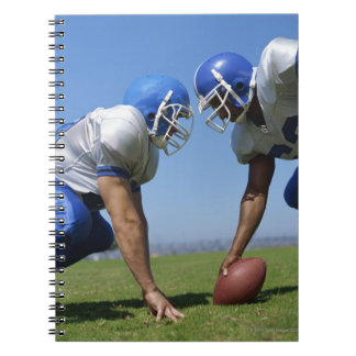 side profile of two football players playing on spiral note books