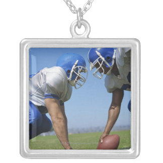 side profile of two football players playing on square pendant necklace