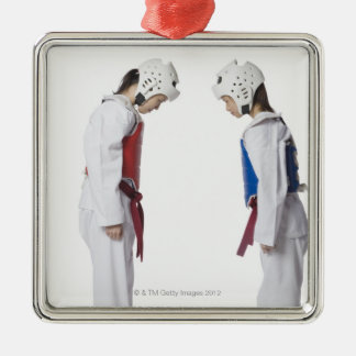Side profile of two taekwondo players bowing metal ornament