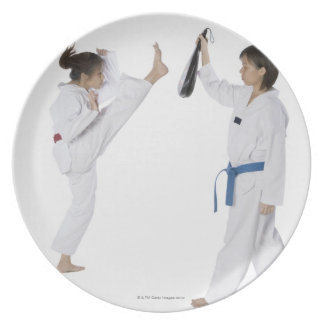 Side profile of two young women practicing dinner plate