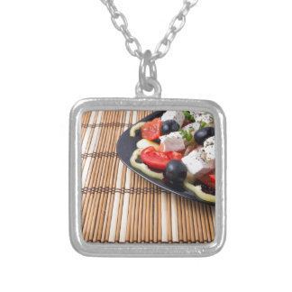 Side view of fresh vegetarian salad on plate silver plated necklace