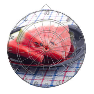 Side view of juicy red watermelon pieces dartboard with darts