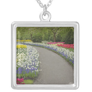 Sidewalk pathway through tulips and daffodils, 2 square pendant necklace