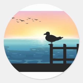 Sihouette bird at sea classic round sticker