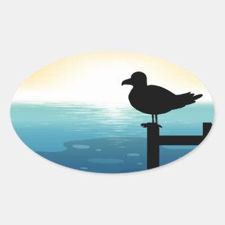 Sihouette bird at sea oval sticker