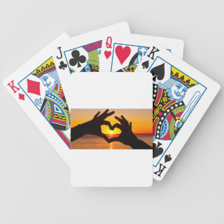 Silhouette hand in heart shape and sunrise over th bicycle playing cards