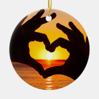 Silhouette hand in heart shape and sunrise over th ceramic ornament