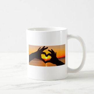 Silhouette hand in heart shape and sunrise over th coffee mug