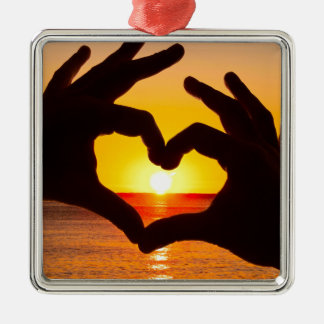 Silhouette hand in heart shape and sunrise over th metal ornament