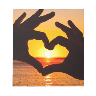 Silhouette hand in heart shape and sunrise over th notepad
