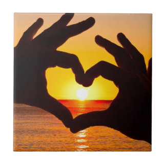 Silhouette hand in heart shape and sunrise over th tile