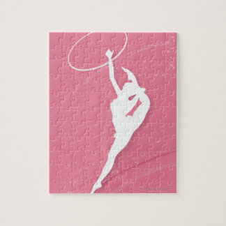 Silhouette of a female gymnast performing with a jigsaw puzzle