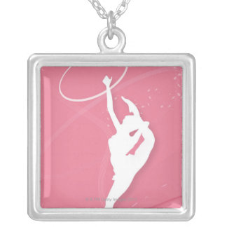 Silhouette of a female gymnast performing with a silver plated necklace