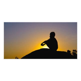 Silhouette of boy sitting o rock card