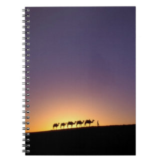 Silhouette of camel caravan on the desert at spiral notebook