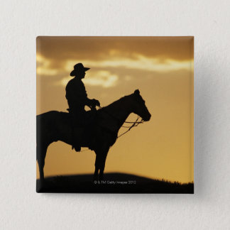 Silhouette of cowboy on horseback at sunset or button