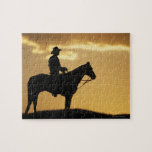 Silhouette of cowboy on horseback at sunset or jigsaw puzzle