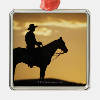 Silhouette of cowboy on horseback at sunset or metal ornament
