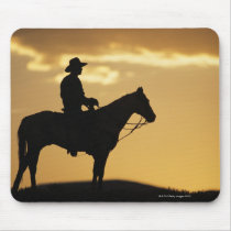 Silhouette of cowboy on horseback at sunset or mouse pad