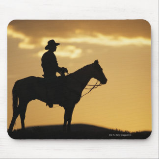Silhouette of cowboy on horseback at sunset or mousepads