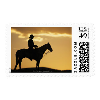 Silhouette of cowboy on horseback at sunset or postage stamp
