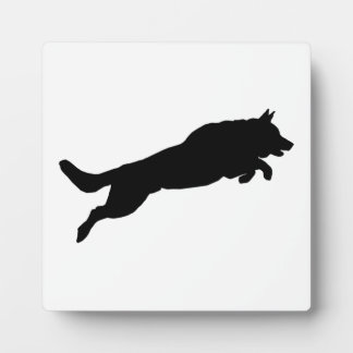 Silhouette of German Shepherd Dog Jumping over Display Plaques