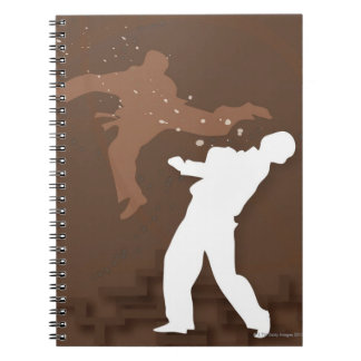 Silhouette of two men practicing karate notebook