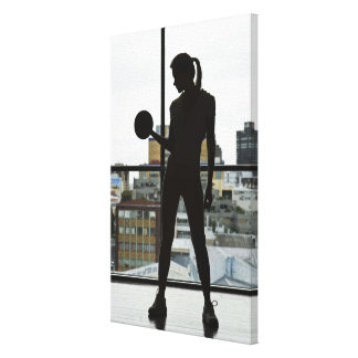 Silhouette of woman lifting weights at gym gallery wrap canvas