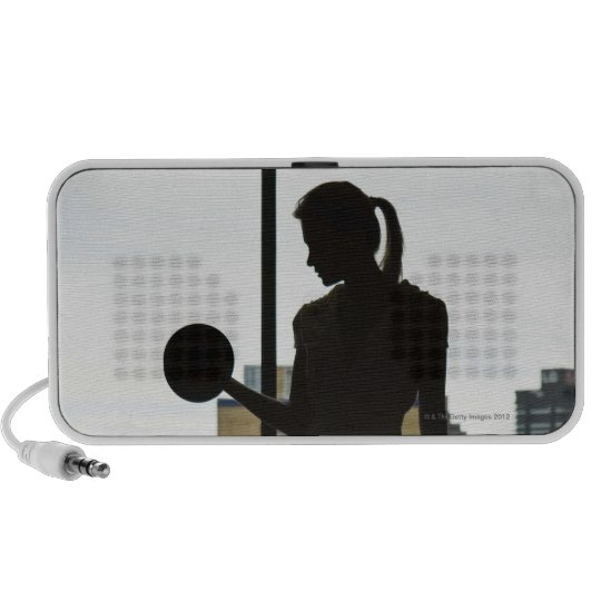 Silhouette of woman lifting weights at gym portable speaker